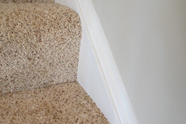 Carpeted stairwell with white baseboard and clean caulking lines