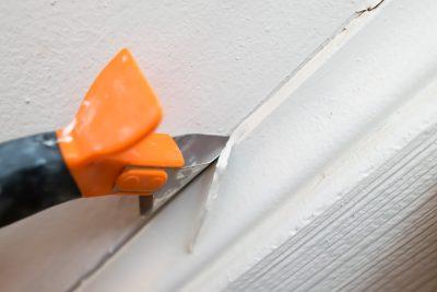 A caulk scraper removing the caulk on a baseboard.