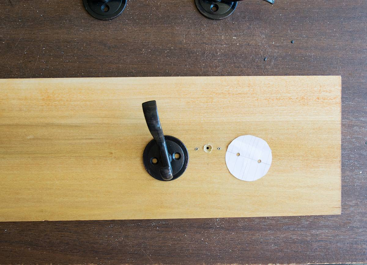 Poplar board with iron hook next to template used for properly positioning hook on board.