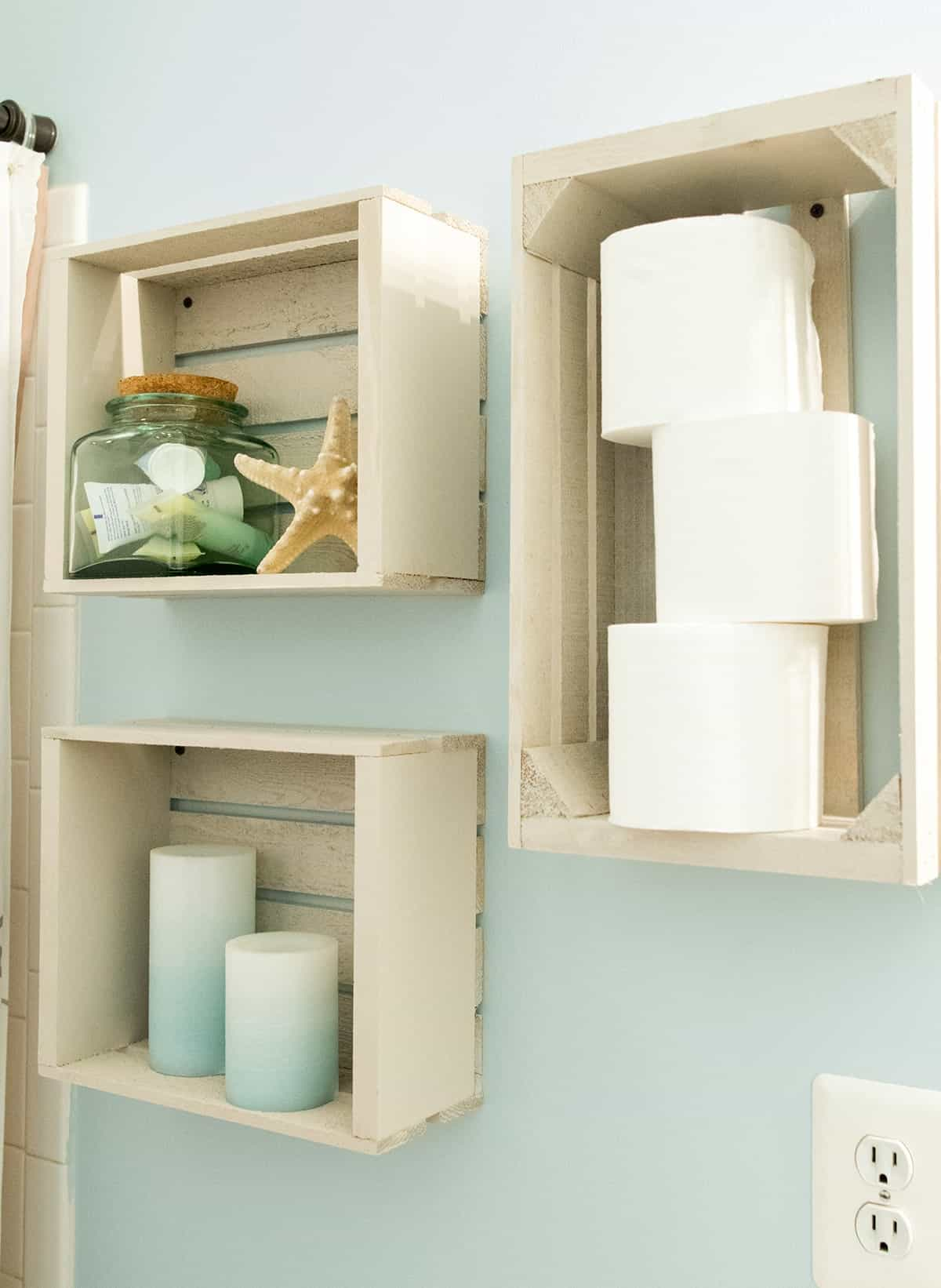 Light wooden crates used for shelving in bathroom with candles, toiletries, and beach decor.