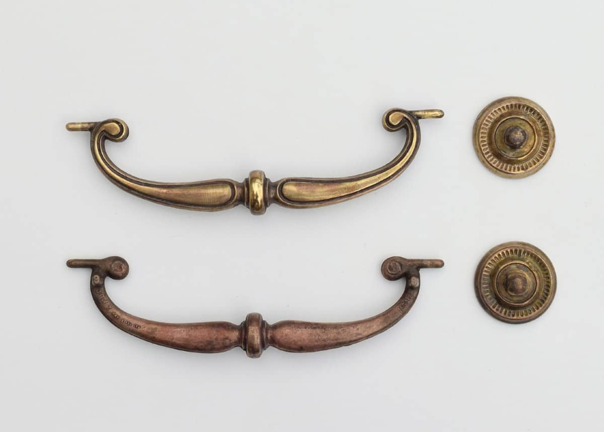 Tarnished brass desk hardware displaying differences in the steps of polishing.