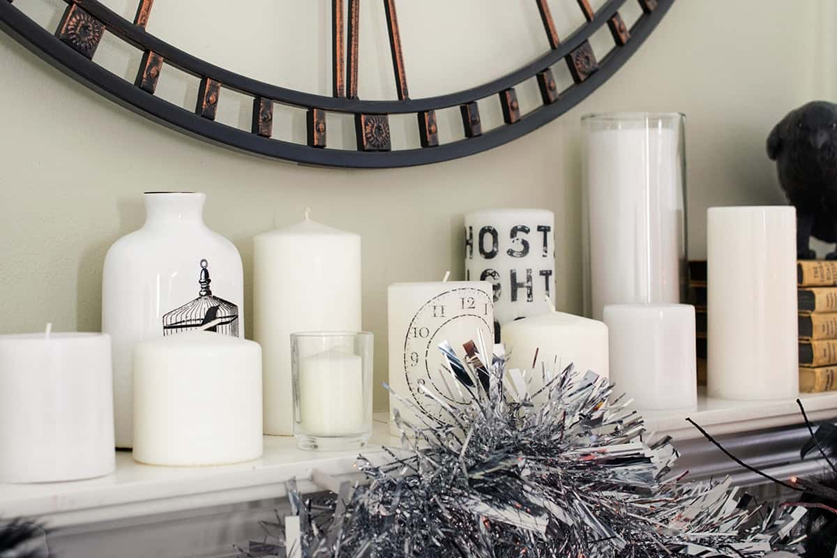 Candles displayed on Halloween themed mantle with DIY stamped images.