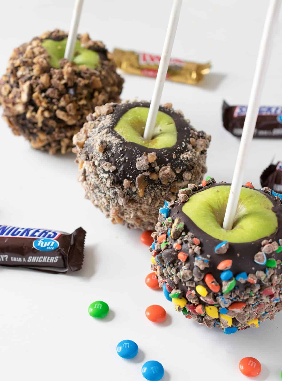 Gourmet candy apples cloaked in chocolate and rolled in assorted candies on white lollipop sticks
