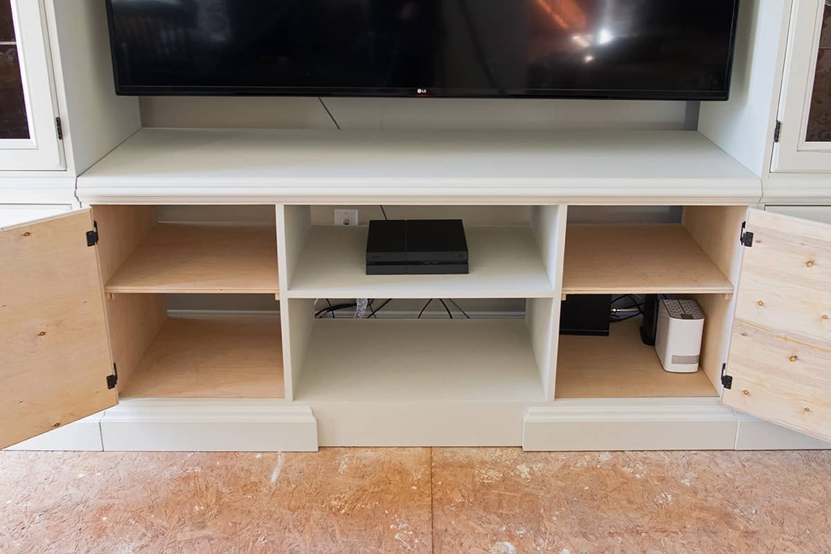 Open doors in built-in new center console of DIY entertainment center project.