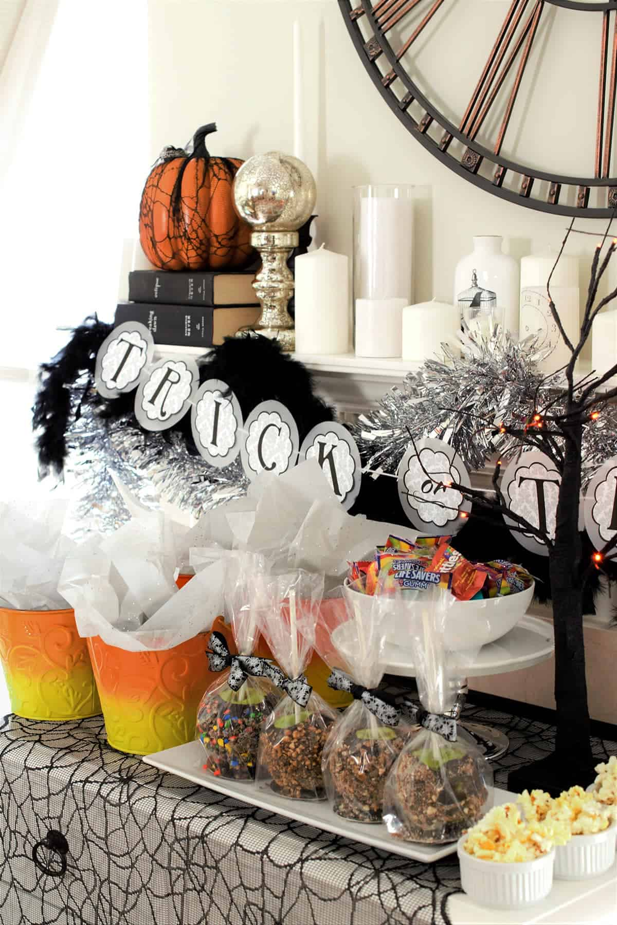 Halloween themed mantle with various decorations and treat table for entertaining guests.