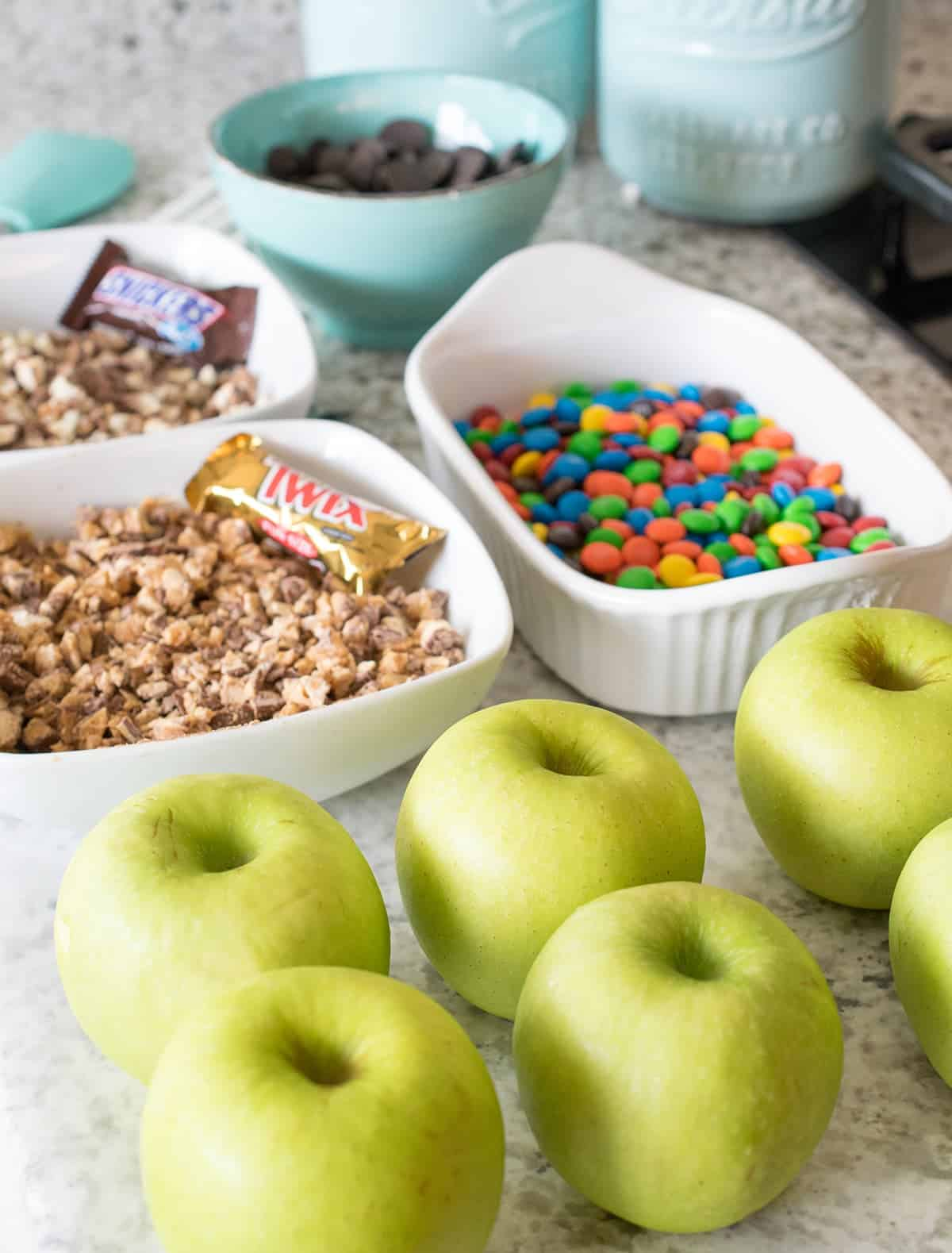 Candy apple rolling station with fresh green apples, assorted baking dishes with m&m's, crushed twix candy bars, snickers, and chocolate chips