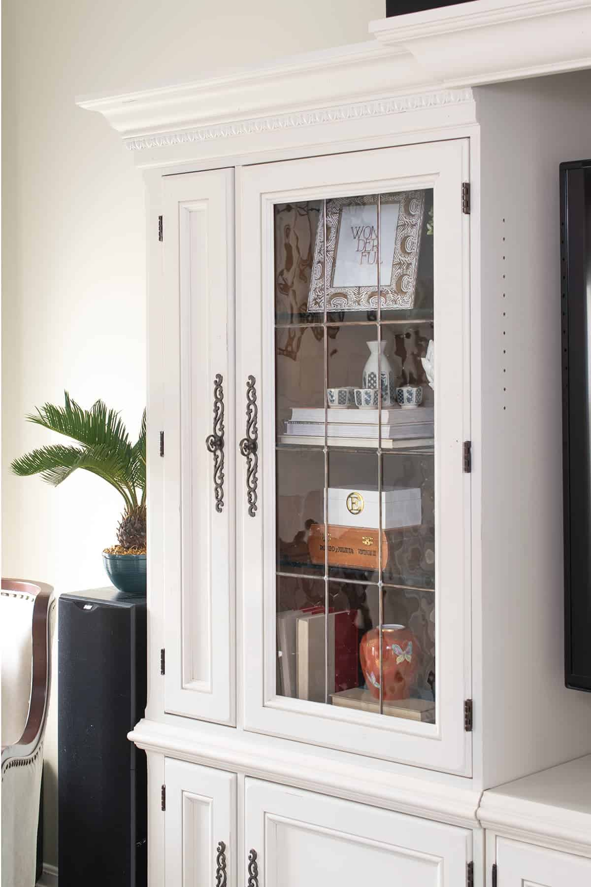 painted white entertainment center  with bookshelves with leaded glass doors
