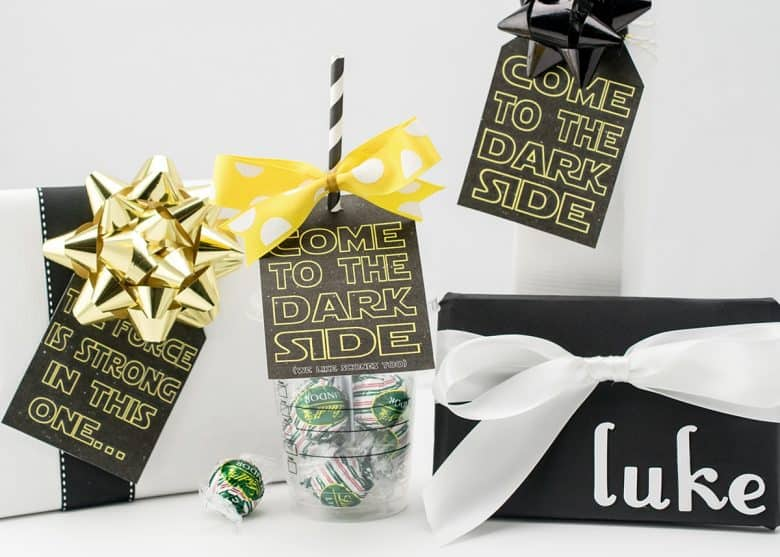 Star Wars printable gift tags on black and white wrapped gifts with gold bows and reusable cup gift.