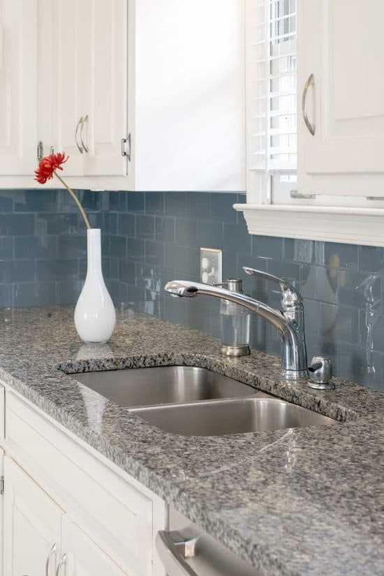 Kitchen with blue tile backsplash, white cabinets, and gray granite countertops.