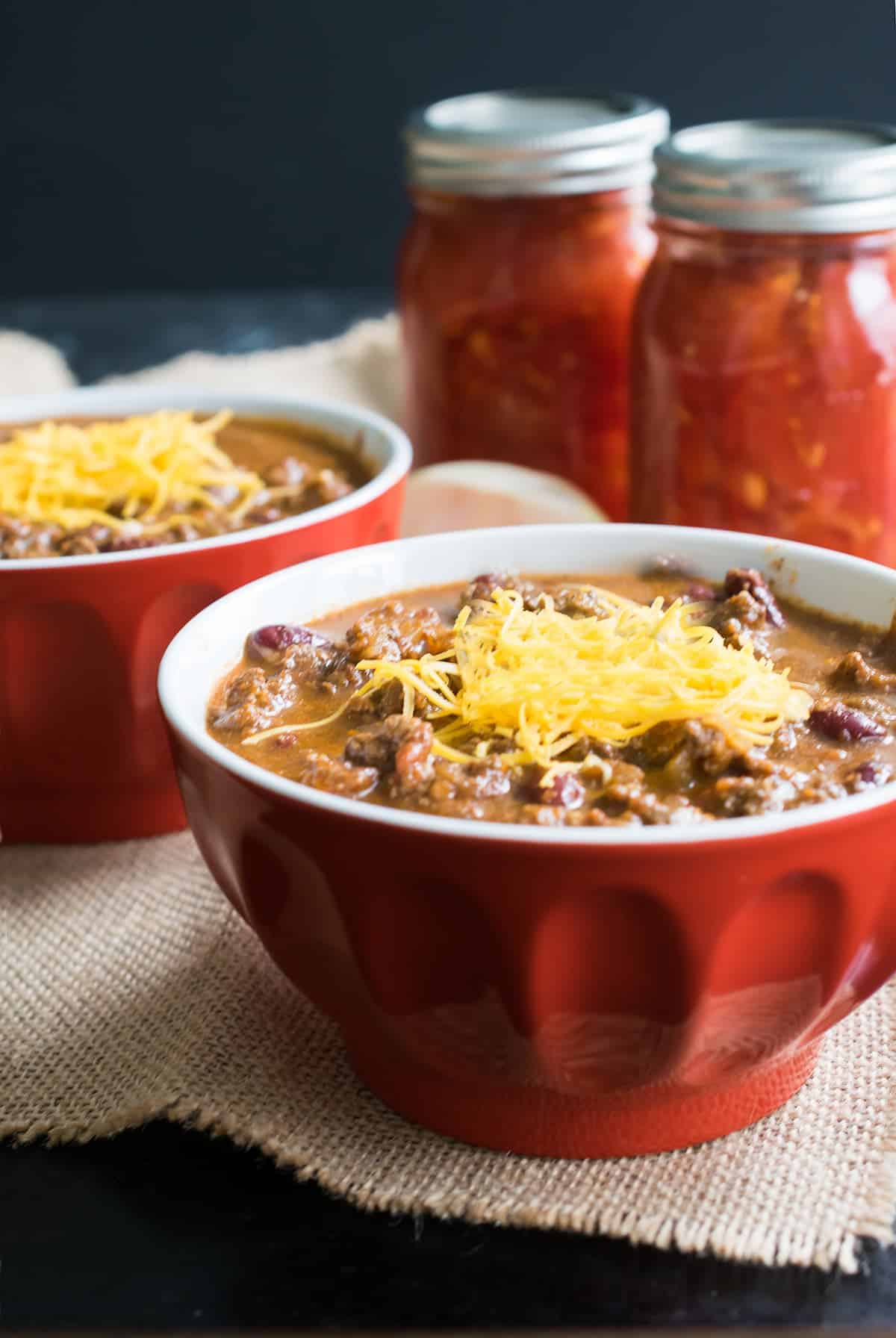 Made from scratch Authentic Cincinnati Chili Recipe- served in red bowls with jarred tomatoes in background
