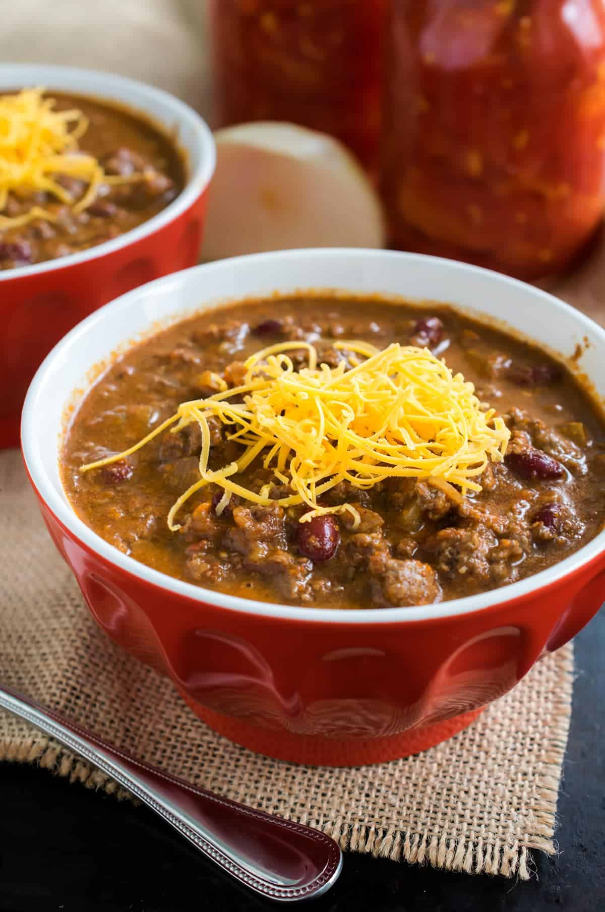 Hearty and comforting Cincinnati style chili with freshly grated cheddar in red bowl on burlap placemat with spoon