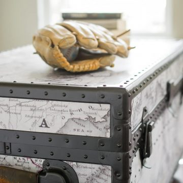Side shot of antique trunk makeover with rivets, metal sides, and map added. Baseball glove on top of footlocker.