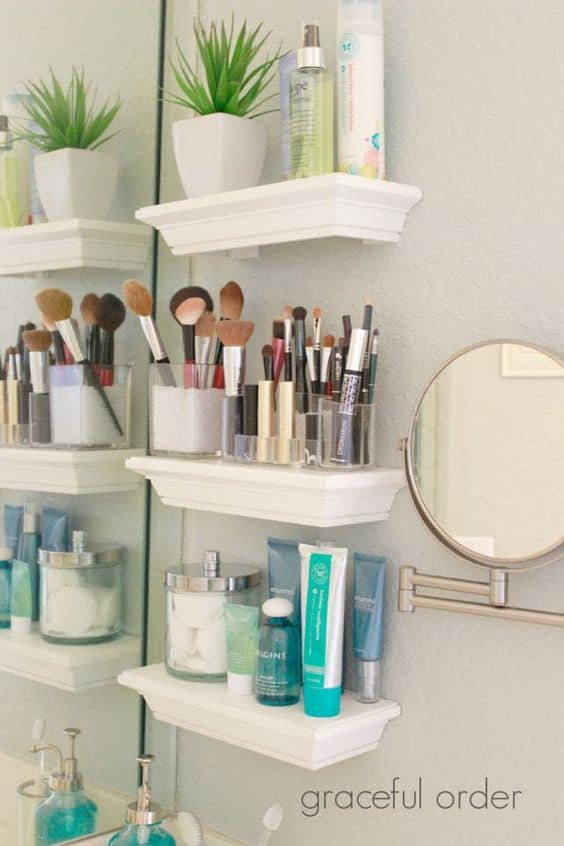 White free-floating shelves on bathroom wall used for storing makeup brushes, toiletries, and small potted plant.