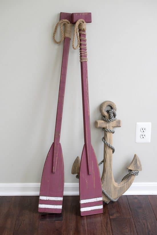 Maroon boating oars propped on soft gray wall before refining for budget friendly coastal decor.