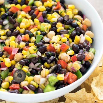 Corn and black bean salad in a bowl with vinaigrette dressing.