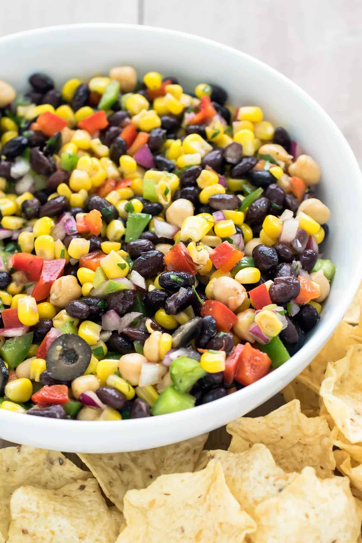Heaping bowl of chopped salad with beans, corn, cilantro, fresh chopped veggies, olives, and vinaigrette.