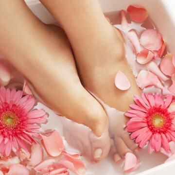 Feet in a foot bath with rose petals in water.