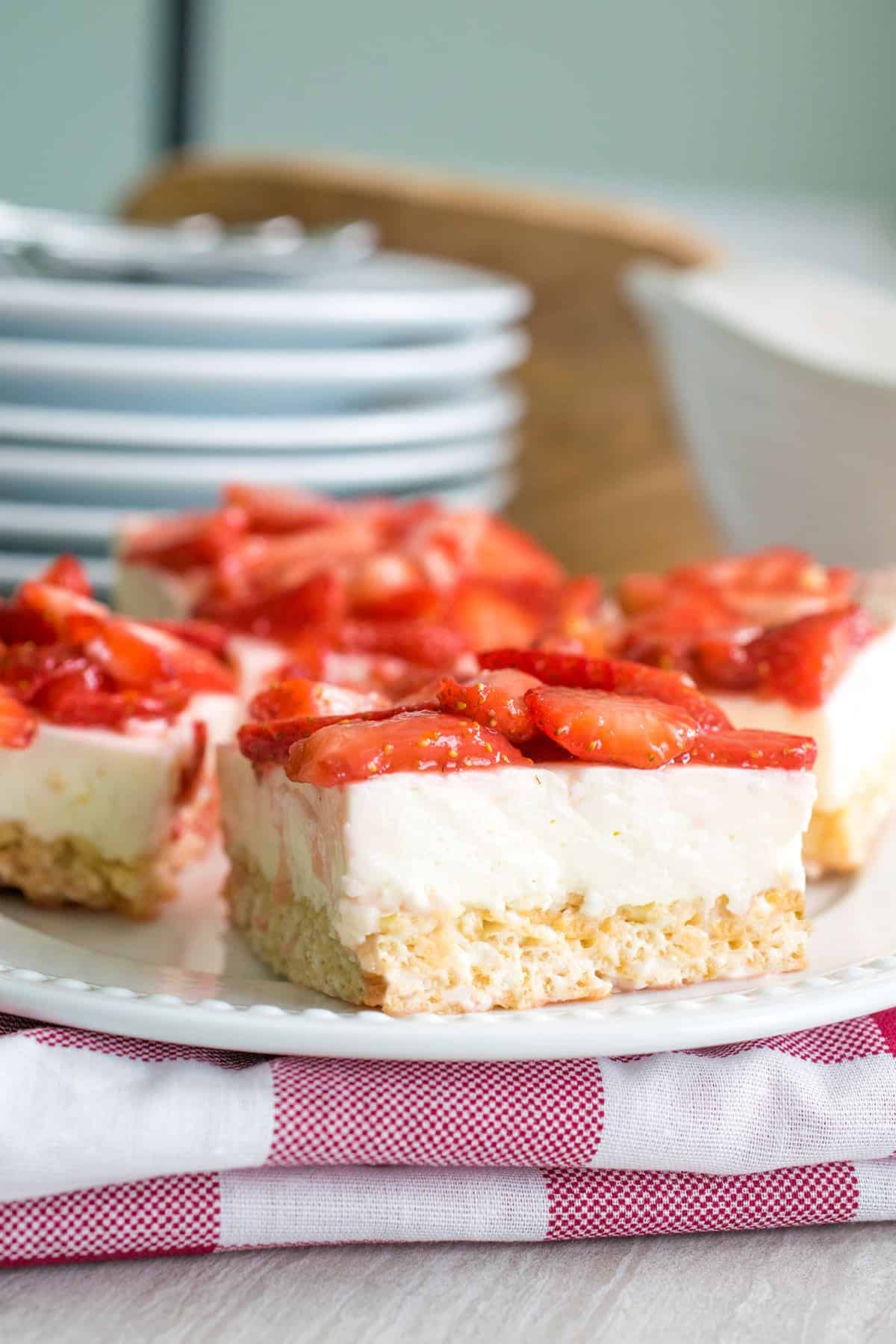 Strawberry cheesecake Rice Krispie Treat squares with stack of white plates on red checkered cloth