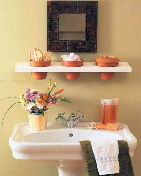 Mini recessed clay flower pots set in white free-floating shelf on bathroom wall for storage.