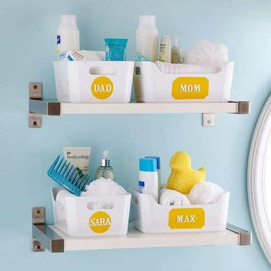 White and metal free-floating shelves in bathroom with individual personalized baskets for the whole family.
