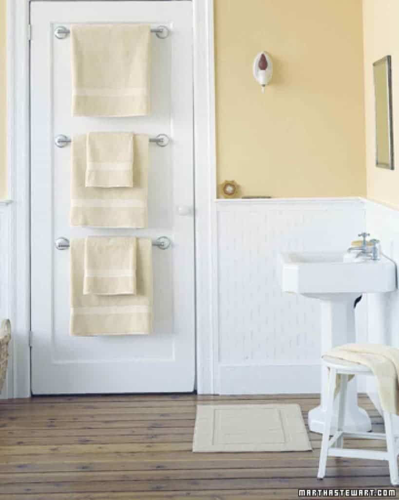 Towel bars mounted on back of white bathroom door with hanging yellow towels