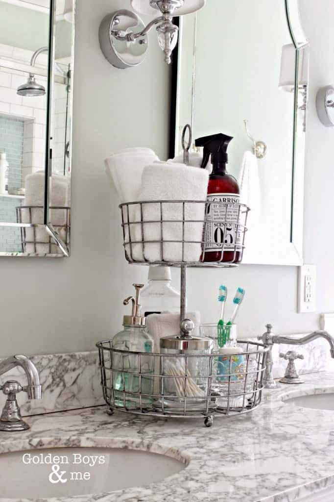 Metal basket tiered tray used for organizing bathroom items for small counter space.