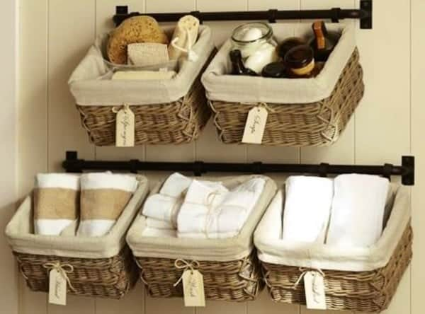 Cast iron rods mounted in bathroom with lined hanging baskets storing linens and toiletries.