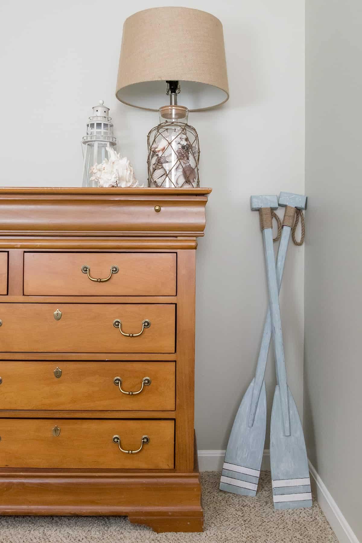 Soft blue white washed boating oars in bedroom corner by dresser
