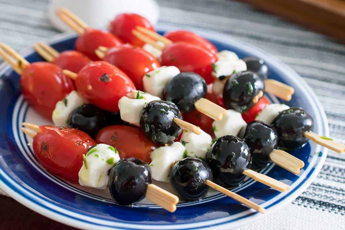 Blue plate with quick antipasto appetizer skewers of grape tomatoes, mozzerella, black olives and herbed olive oil.