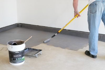 Man painting a garage floor with a roller.