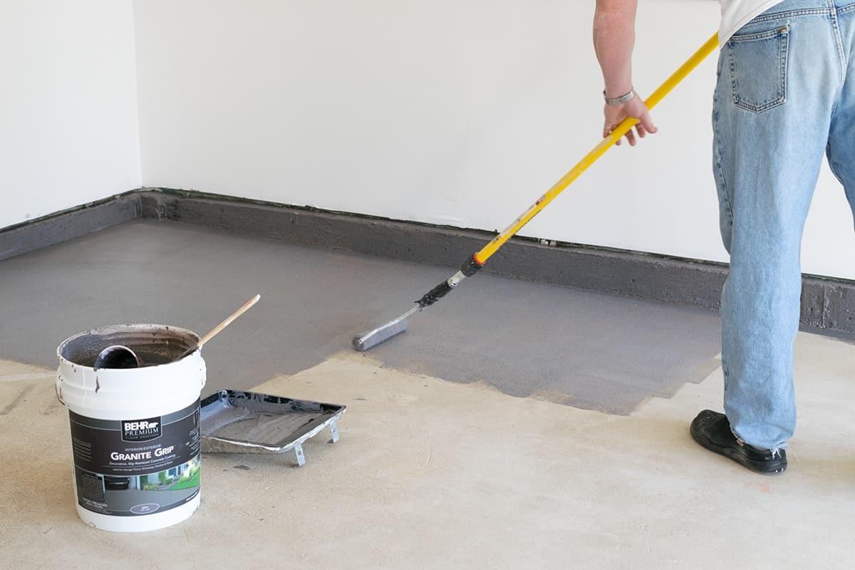 Man applying Behr Premium Granite Grip non-slip coating to garage floor with adhesive roller.