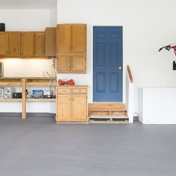 Garage with gray painted floor that is clean and organized.