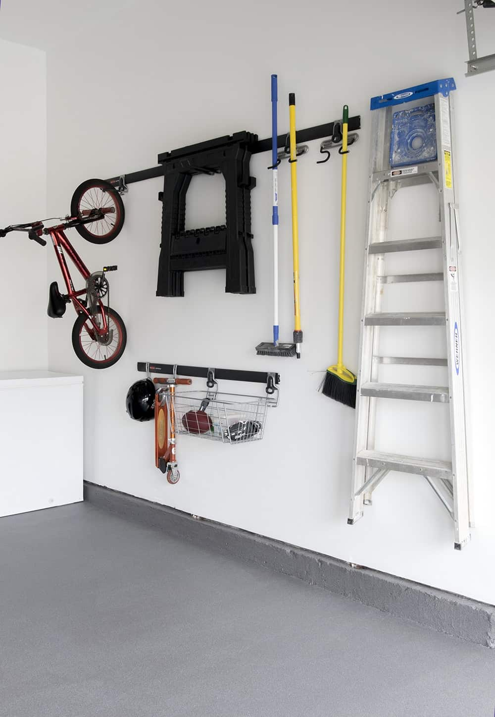 Non- slip floor in residential garage below organized hanging wall with ladders, toys, and cleaning supplies.