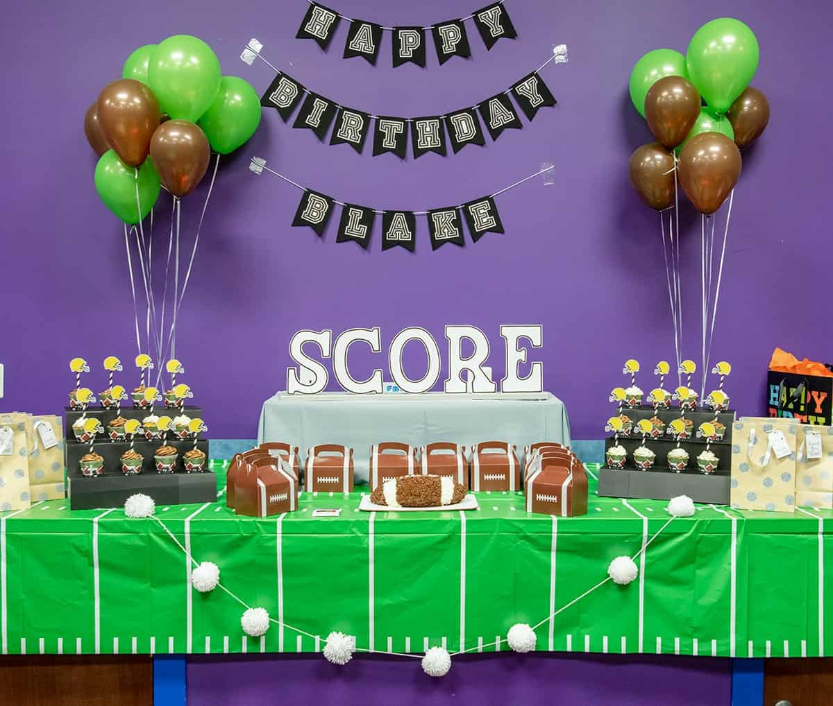 Football themed kid's birthday party table setup with accompanying football themed cakes and decorations.