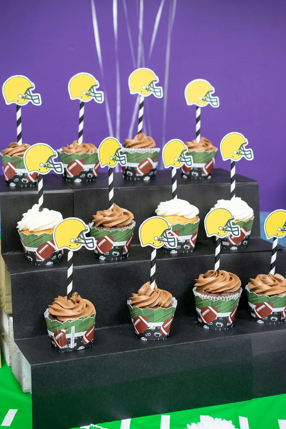 Football themed cupcakes on sports fan bleacher inspired stand with helmet cupcake toppers.