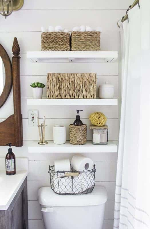 Three white free-floating shelves above commode with wicker storage baskets, toiletries, and small linens.