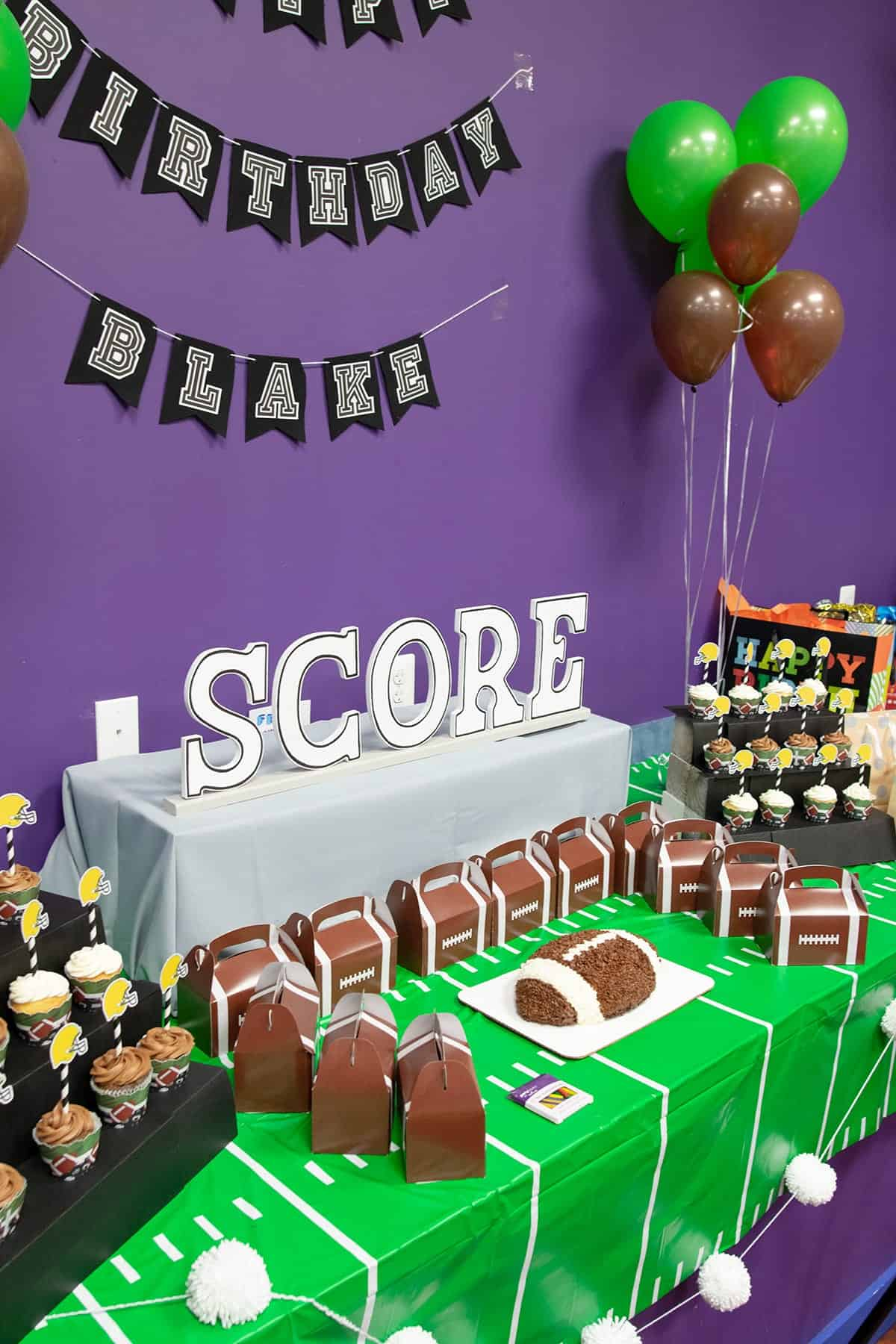 Football themed table with yard line tablecloth, football cake and cupcakes , balloons, and football party favors.