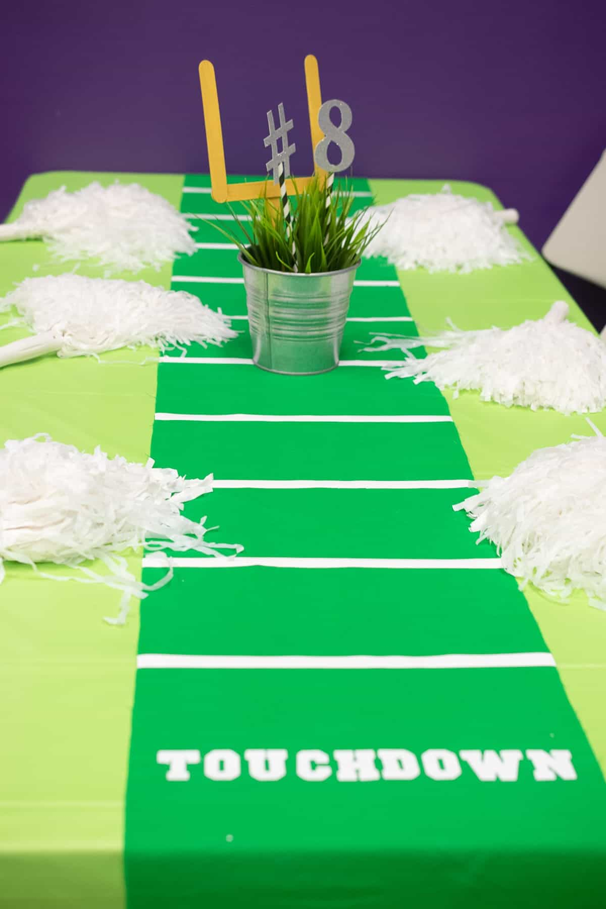 Kid's birthday football themed table with yard line table runner, pom-poms, and mini potted field goal.