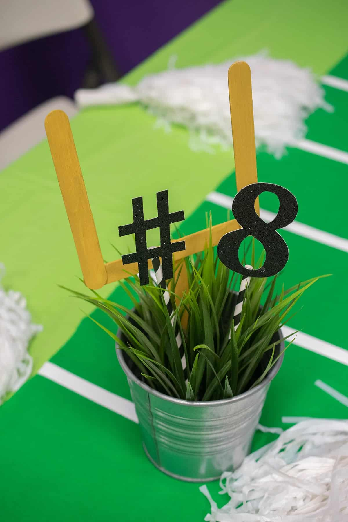 Kid's party table centerpiece mini field goal made of popsicle sticks in small metal potted grass bucket.