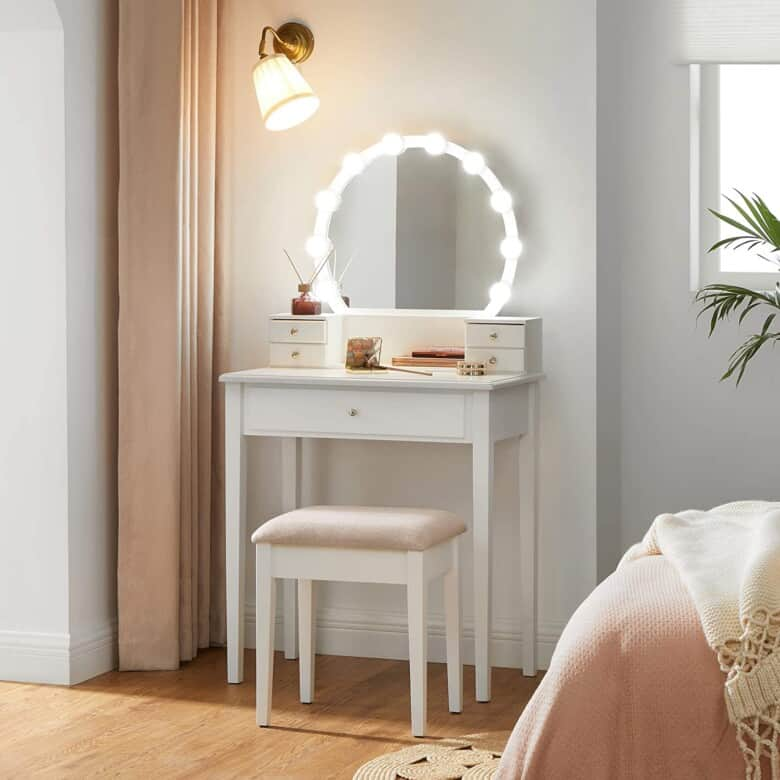 Lighted Vanity with mirror and stool in a bedroom.