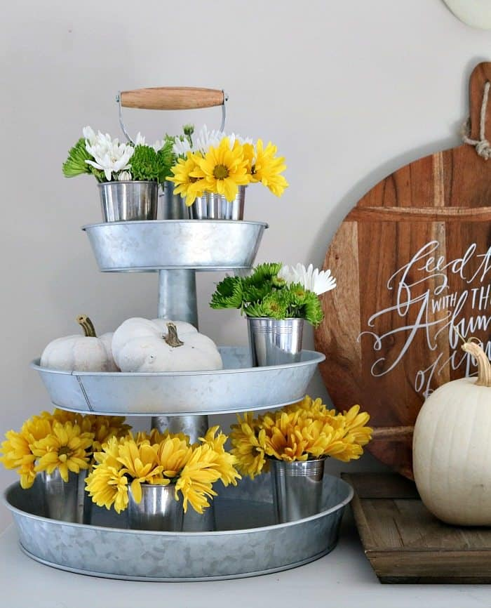 Metal 3 tiered tray with pumpkins and mini buckets with yellow flowers and greenery.