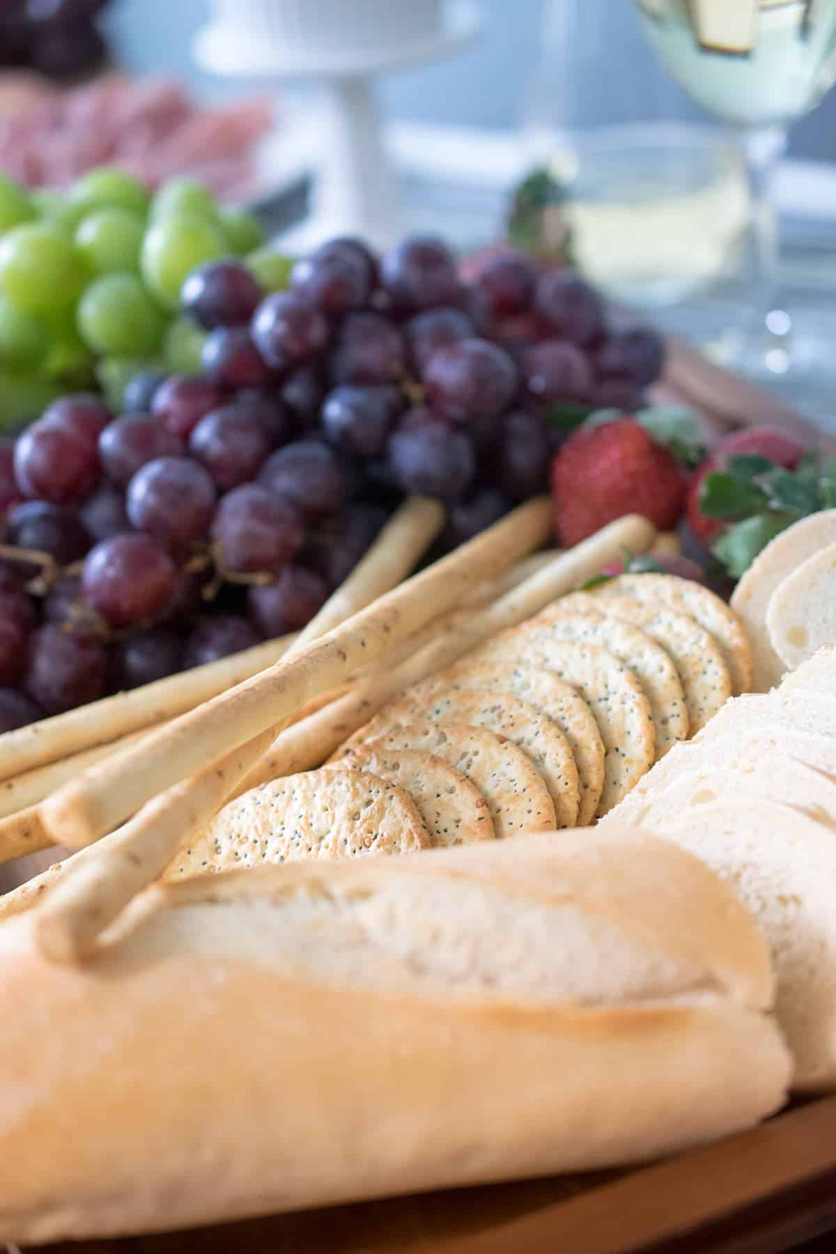Party tray with freshly sliced baguette, crackers, strawberries, and grapes