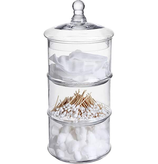 Stacked glass containers with cotton swabs, q-tips, and cotton pads in them.