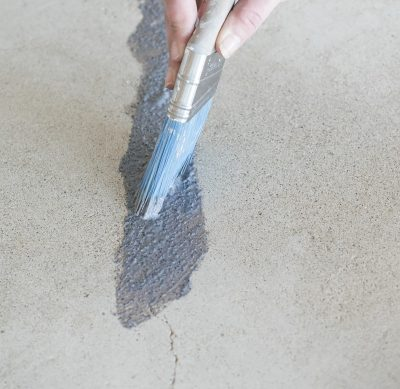 Brushing Behr Granite Grip on floor with a paint brush.