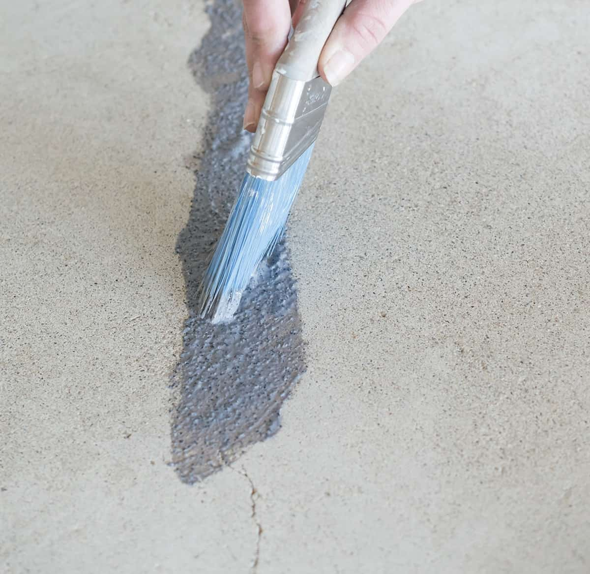 Woman using a paint brush and Granite Grip to fill in hairline cracks in concrete garrage.