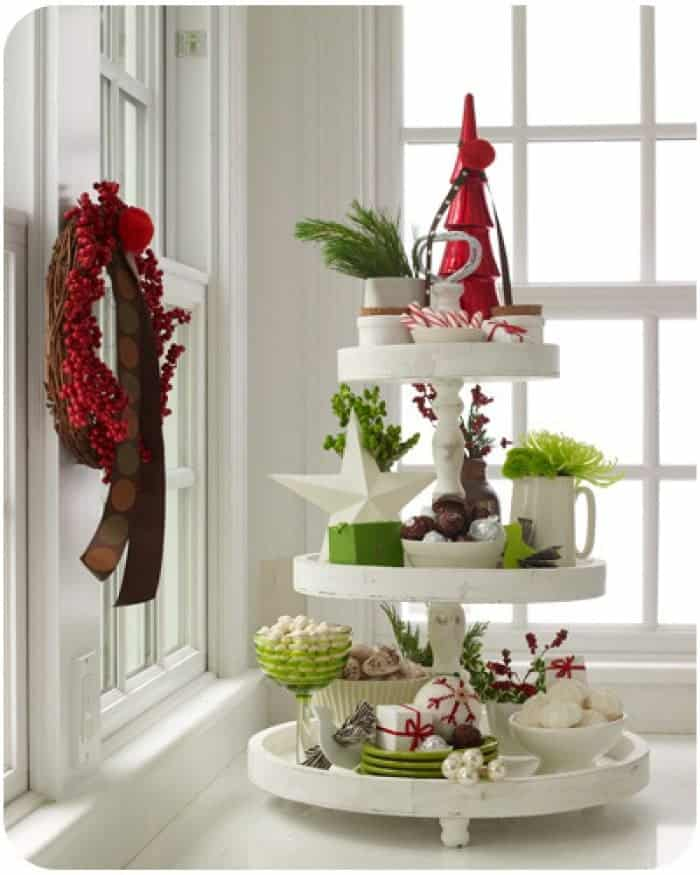 White wooden 3 tiered tray with assortment of holiday decorations and festive treats.