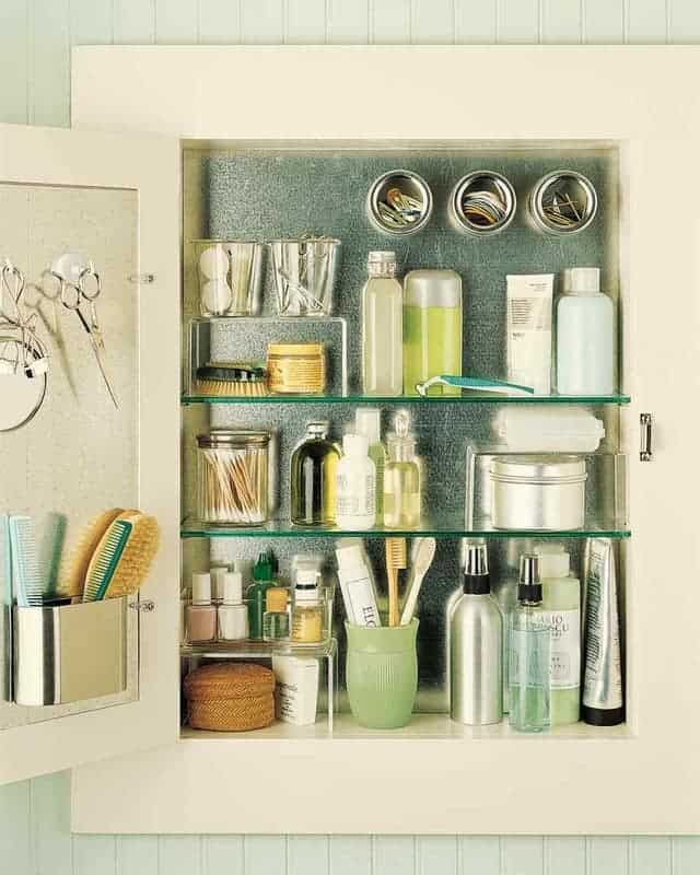 Open medicine cabinet with glass shelves and magnetic galvanized metal sheets mounted for extra storage.