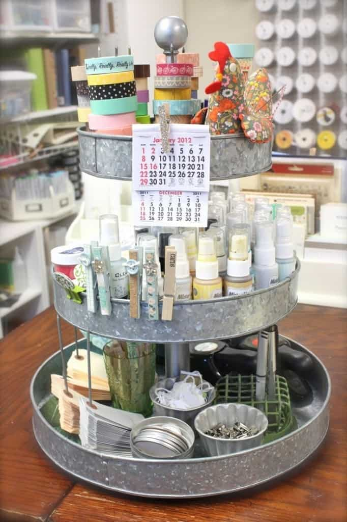 Metal 3 tiered tray for organizing craft supplies with paints, ribbon spools, tags, clothes pins, and small calendar.