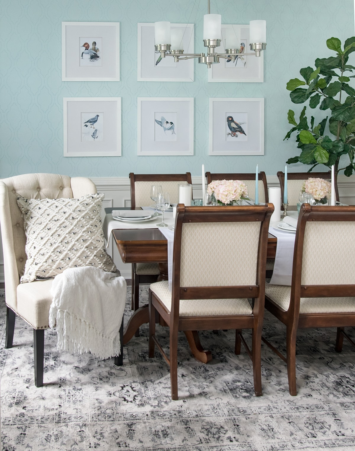 Classic chic dining room with area rug, natural accents, gray curtains, black lanterns, and soft blue walls.