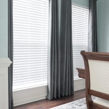 Two windows with blinds closed and grey curtains on either side.
